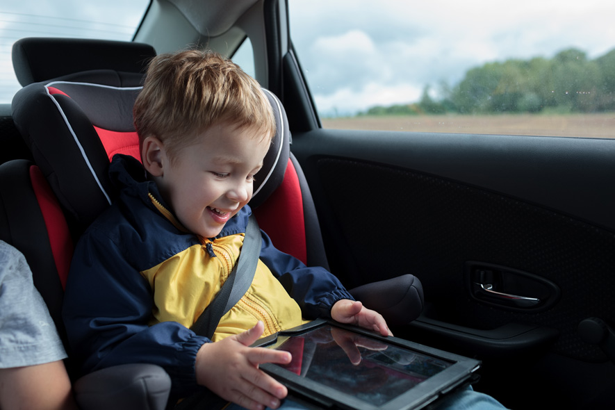 Kid in car playing with tablet