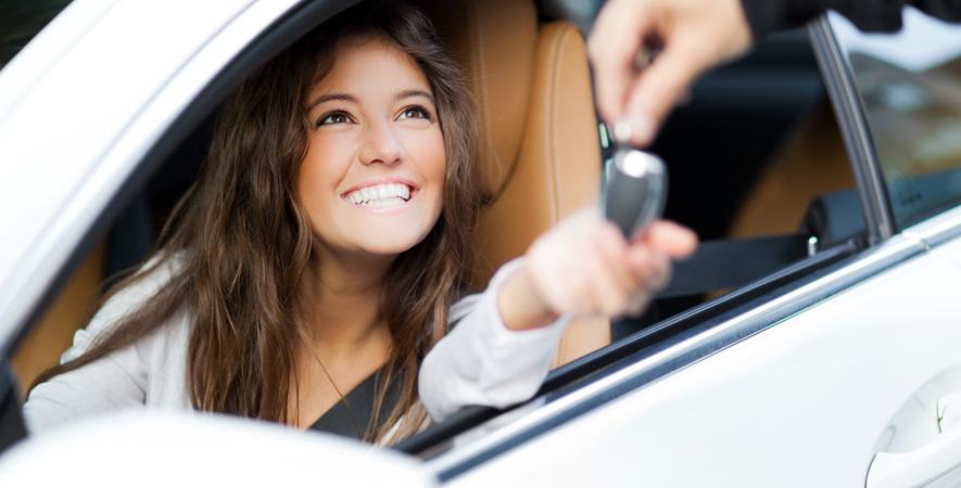Women sitting in car, receiving keys from dealer