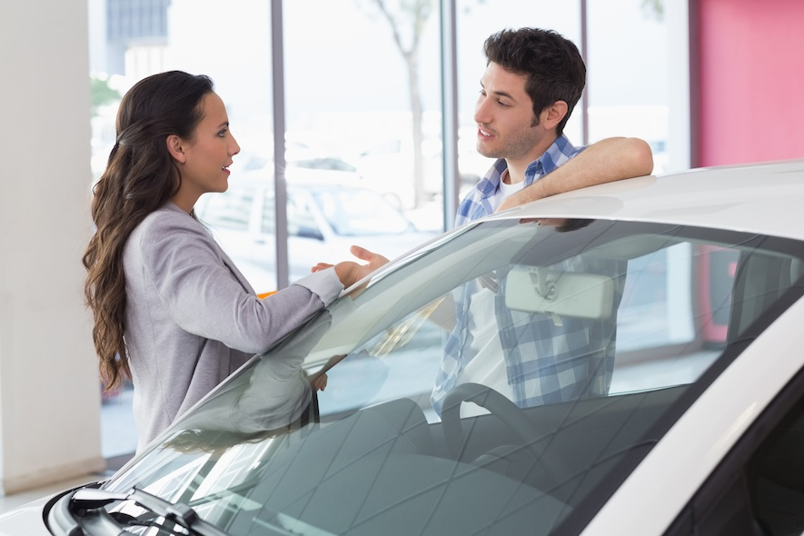 couple discussing what car to buy at a dealership