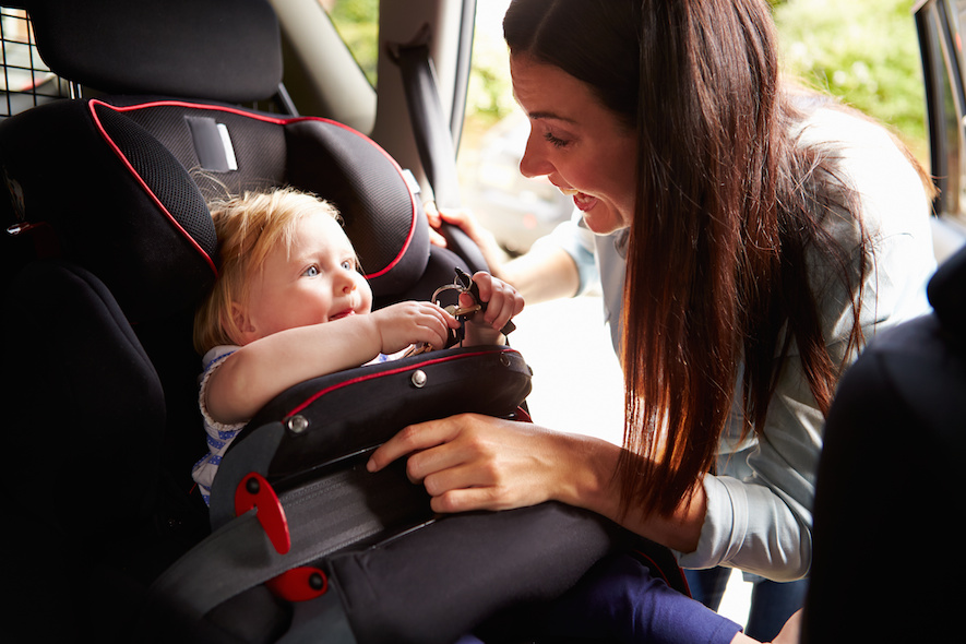 mom buckling child into car seat