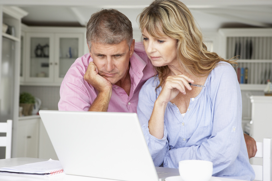 middle aged couple looking at computer, comparing car insurance quotes