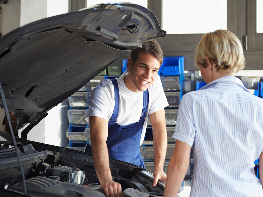 mechanic helping customer with engine repair