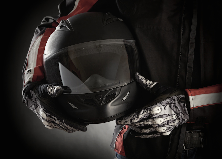 motorcycle helmet being held by a man in a leather jacket
