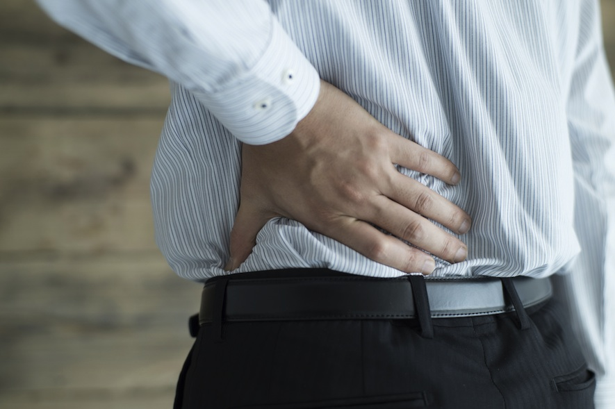 a man rubbing his lower back as a result of backaches