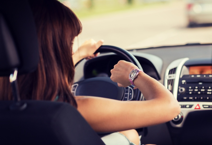 woman looking at her watch in the car