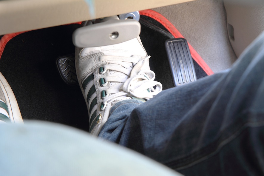 A man's foot on the car brake