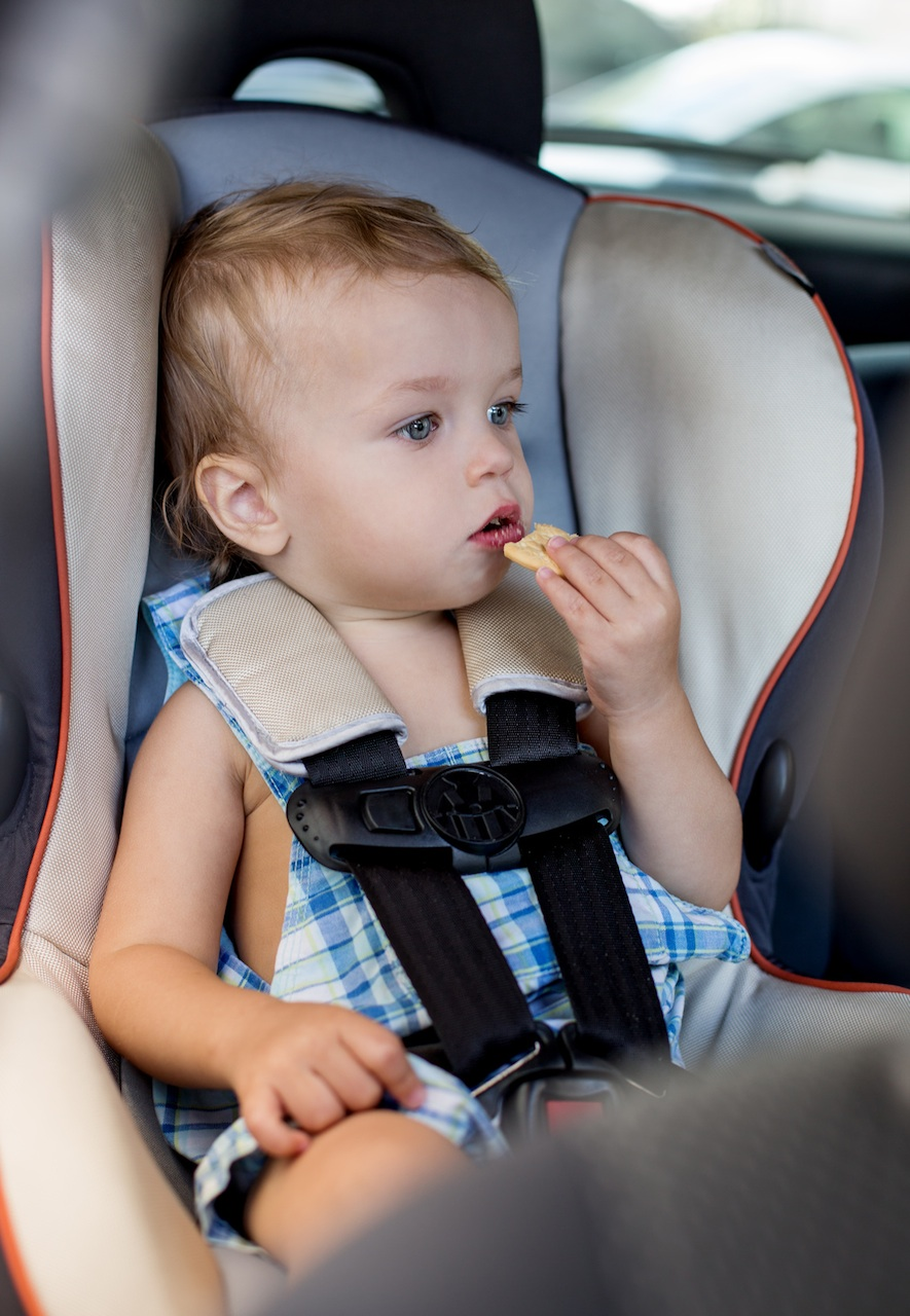 Toddler having a snack in a car seat