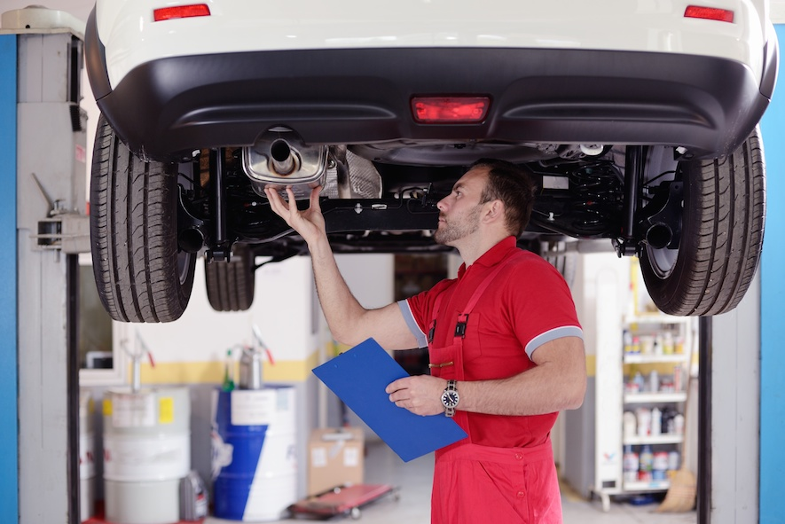mechanic inspecting muffler