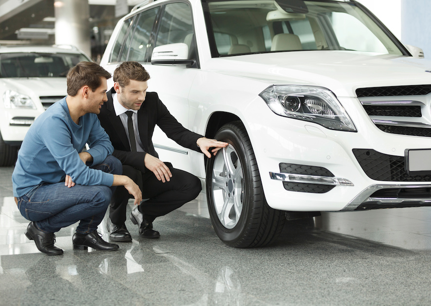 dealer pointing out tires to customer before buying a car at the car dealership