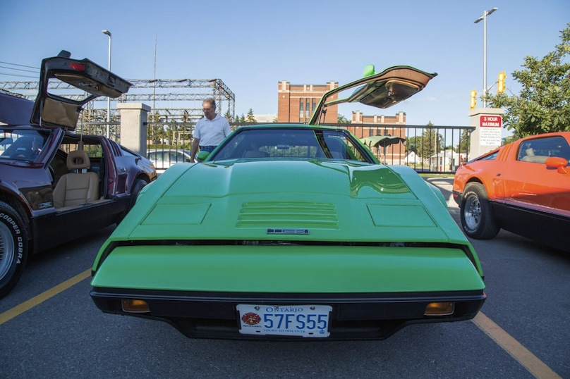 Front view of a green DeLorean with the door open
